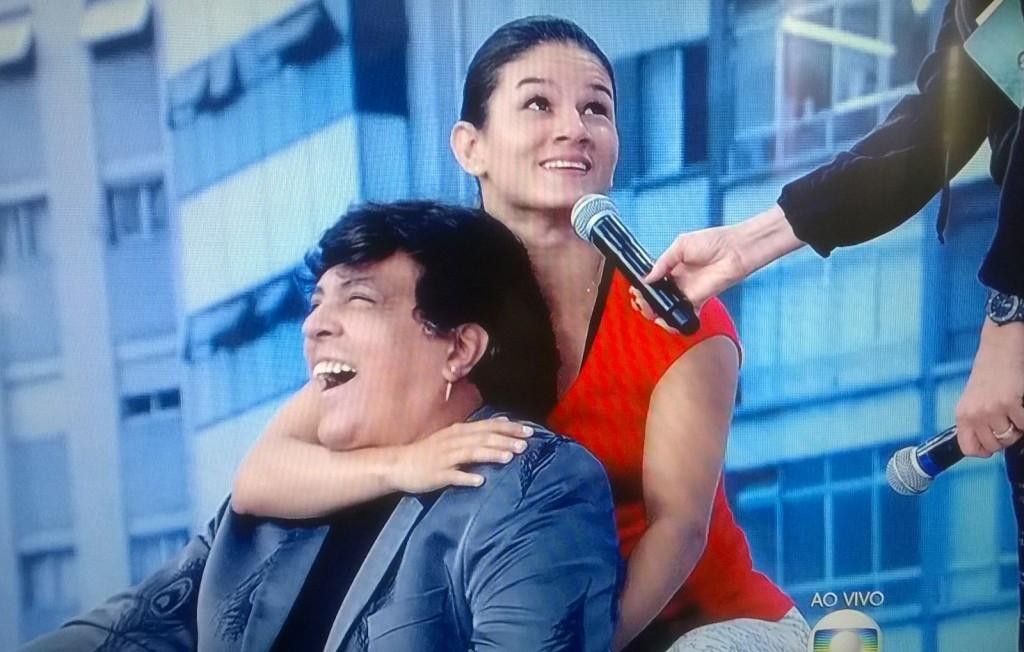 Monique Bastos mostrou como imobilizou o assaltante, numa simulação com o cantor Sidney Magal
